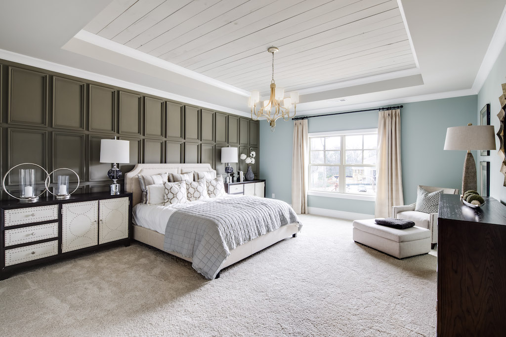 The bold board and batten wall combined with a shiplap tray ceiling makes this a captivating master bedroom.