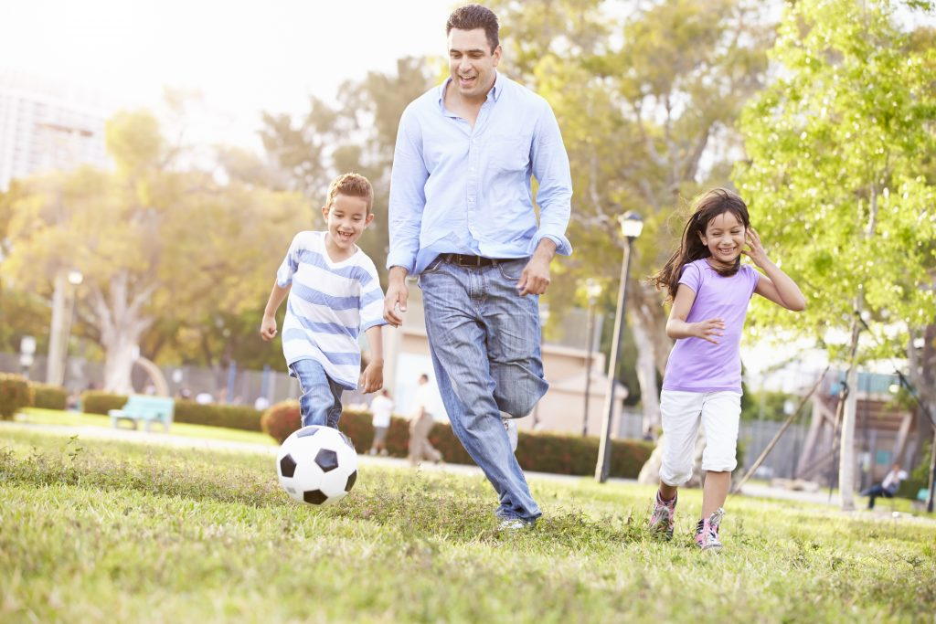 Father With Children Playing Soccer In Park Together